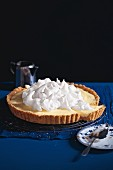 Lemon tarts topped with whipped cream, sliced
