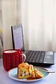 A slice of Cassata Siciliana next to a laptop