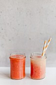 Melon smoothies in screw-top jars with straws