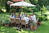 Gäste an gedecktem Tisch unter Sonnenschirm im Garten