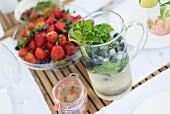 Erfrischungsgetränk mit Kräutern in Glaskrug und frische Beeren auf Glasschale