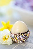 A marzipan egg with chocolate glaze and sugar sprinkles for Easter