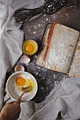 A baking scene with eggs, flour, a recipe book and a whisk