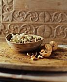Cashewkerne, Pistazien und Walnüsse in Holzschale und daneben