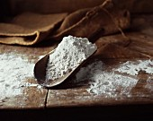 Wheat flour in a wooden scoop on an old wooden table