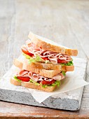A stack of ham sandwiches with lettuce and tomato is