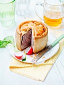 A sliced pork pie with radishes and beer