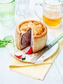 Schweinefleisch-Pastete angeschnitten mit Radieschen und Bier