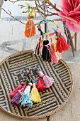 Colourful handmade woollen tassels on a raffia plate and hanging on a twig