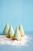 Spongecake Christmas trees with green icing and grated coconut