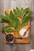 Fresh bay leaves, peppercorns and salt on a chopping board