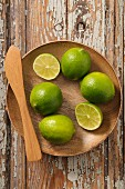 Limes, whole and halved, in a wooden bowl