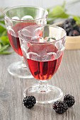 Two glasses of blackberry liqueur and fresh blackberries