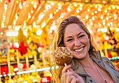 A young woman at a funfair holding a toffee apple