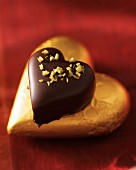 A marzipan heart coated in chocolates topped with pistachios