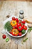 Various tomatoes in a bowl with thyme