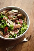 Mixed leaf salad with ham and bread