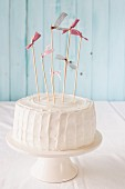 A white birthday cake with pink flags on a cake stand