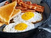 Spiegeleier mit Bacon und Toast in der Pfanne