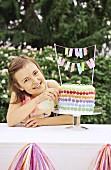 Mädchen neben Geburtstagstorte mit bunten Schokolinsen im Garten