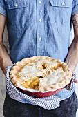 A man holding a peach pie