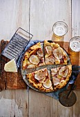 Pizza with ham, pears and fontina cheese on a wooden board (seen from above)