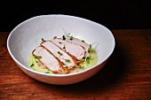 Pork with apples and pears on a green foam sauce