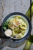 Courgette pasta with pesto and ricotta sauce garnished with pine nuts and grated Parmesan cheese