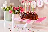 Children's birthday cake with chocolate glaze and chocolate beans with tulips in the background