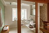 Blick durch geöffnete Glastür in modernes Bad, seitlich Waschtisch mit Ablagen