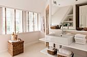 Waschtisch mit Aufbaubecken und Ablagen, im Hintergrund Rattan Truhe mit Aufgusseimer vor Fenster mit Jalousie