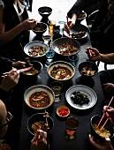 Essende Menschen an gedecktem Tisch mit verschiedenen chinesischen Gerichten
