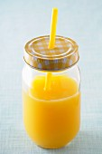 Orange juice in a screw-top jar with a straw