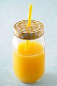 Orange juice in a screw-top jar with a straw