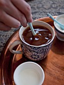 Milk and sugar being stirred into a cup of coffee