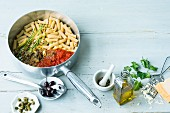 Penne pasta with sauce ingredients in a saucepan