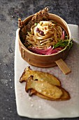 Raw kohlrabi spaghetti with bean sprouts and king trumpet mushrooms in soy sauce with sesame seed crackers (Asia)