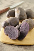Purple potatoes on a wooden board