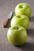 Three green apples on grey tablecloth