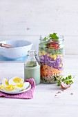 A layered rainbow salad in a jar with an avocado dressing
