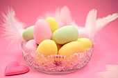 Pastel coloured Easter eggs with feathers in a glass bowl