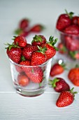 Freshly washed strawberries in a glass on a white wooden surface