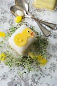 A petit four decorated with a chick, thyme and sugar eggs