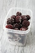 Frozen blackberries in a plastic container
