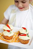 Kid holding Carrot Tops Carrot Cup Cakes