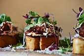 Bruschetta with braised beef, cress and grated Parmesan cheese
