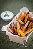 Winter vegetable chips in a wooden basket with a bowl of herb quark