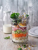 Layered watercress and raw vegetable salad with tender wheat in a jar
