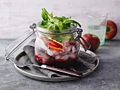 A layered soused herring with beetroot in a jar