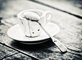 Ausgetrunkene Espressotasse mit Löffel (Schwarzweissaufnahme)